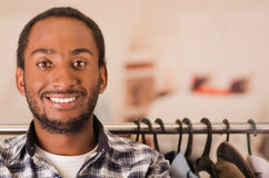 Headshot young man smiling to camera, standing in front of clothing rack, fashion concept Stock Images