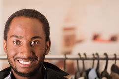 Headshot young man smiling to camera, standing in front of clothing rack, fashion concept Royalty Free Stock Photography