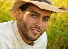 Headshot of young man wearing a cowboy hat. Headshot of young man sitting in a grassy field wearing a cowboy hat Stock Photos