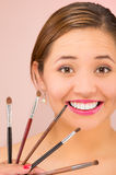 Headshot young pretty hispanic woman brunette with red lipstick holding up selection of makeup brushes, pink background Stock Images