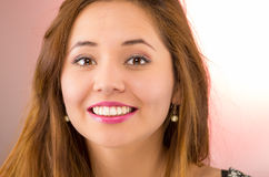 Headshot young pretty hispanic woman brunette with red lipstick, smiling to camera, pink background Stock Images