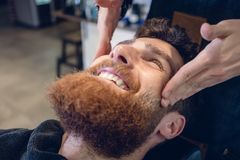 Young bearded man smiling during a relaxing temple massage royalty free stock photo