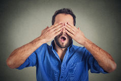 Headshot young scared man covering eyes with hands wide open mouth Stock Photo