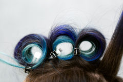 Headshot of a young woman with hair curlers in a beauty salon. Stock Images