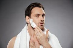Headshot zdrowa mężczyzna kładzenia golenia piana na twarzy, podczas gdy havi fotografia royalty free