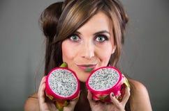 Headshotbrunetten, den mörka nimbusblicken och gräsplanläppstift, hållande två öppna halfs av den rosa pitayaen bär frukt upp med Royaltyfri Bild