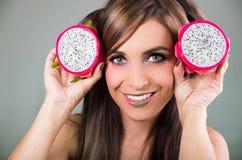 Headshotbrunetten, den mörka nimbusblicken och gräsplanläppstift, hållande två öppna halfs av den rosa pitayaen bär frukt upp med Royaltyfri Fotografi