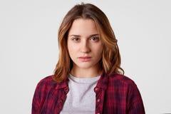 Headshoten av den allvarliga kvinnan har säkert uttryck, bär den rutiga skjortan, tillfällig t-skjorta, står mot vit bakgrund, royaltyfria bilder