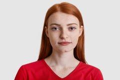 Headshoten av den attraktiva röda haired europeiska kvinnan med fräknig hud, ser allvarligt på kameran, har minsta utgör, bär röt arkivfoto