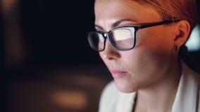 Headshoten av den attraktiva unga affärskvinnan som sent i regeringsställning arbetar på natten bara, en reflexion av datorskärme arkivfilmer