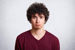 Headshoten av den upprivna attraktiva mannen buktar lägre kant, misshas med negativ nyheterna och att vara ledsen, och besviket,  royaltyfria bilder
