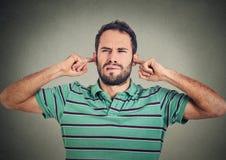 Headshoten misshog mannen som pluggar öron med fingrar, önskar inte att lyssna Arkivbild