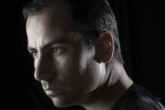 Headshotporträt des jungen Mannes auf hartem Licht des schwarzen Hintergrundes Stockbild