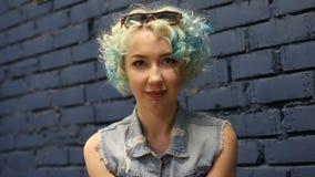 Headshotstående av den härliga blåa haired flickan med lockigt hår som ser kameran stock video