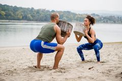 Headsome athlets work out on the beach. Holding tree stumps Royalty Free Stock Images