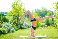 headstand Jeune fille attirante dans les vêtements de sport noirs faisant l'exerc Image stock