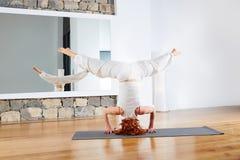 Headstand Sirsasana de la yoga al revés en el gimnasio Imagenes de archivo