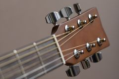 Headstock of acoustic six-string guitar. Headstock with tune machine head of acoustic six-string guitar close-up on black background Royalty Free Stock Image