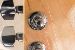 Headstock av den elektriska gitarren, ljust trä, närbild Arkivfoton