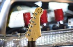 Headstock av den sex klassiska elektriska gitarren för rad på suddig bakgrund Royaltyfri Foto