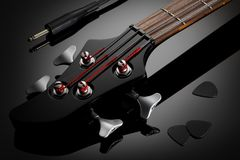 Headstock of electric bass guitar, audio cable and picks Stock Image