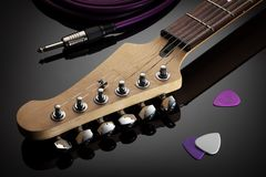 Headstock of electric guitar, jack cable and picks Stock Images