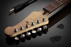 Headstock of electric guitar, jack cable and picks Royalty Free Stock Photos