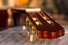 Headstock em notas velhas da música, fim da guitarra acima imagens de stock royalty free
