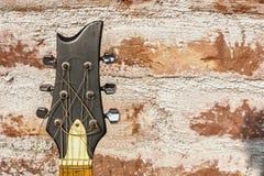 Headstock för akustisk gitarr på bakgrund för textur för tegelstenvägg arkivfoto