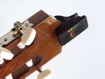 Headstock of the guitar with installed clip-on tuner, that shows. The headstock of the guitar with installed clip-on tuner, that shows the note e Royalty Free Stock Photo