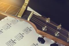 Headstock med capoen av den akustiska gitarren och det grundläggande ackordet Arkivfoton