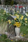 Headstone decorated with artificial flowers on graveyard. Headstone decorated with artificial yellow rose flowers in graveyard Stock Photo