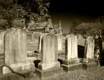 Headstones in cemetery in black and white. Marble headstones in cemetery outside church in black and white royalty free stock images