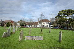 Headstones in a Churchyard with the Village Pub in the background. WOODCHURCH, KENT, UK, 25 JANUARY 2016 - All Saints graveyard with the Bonny Cravat public Royalty Free Stock Images