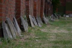Headstones. Forgotten headstones leaning against the wall stock images