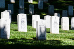 Headstones in a Line at Arlington National Cemetery. White marble headstones with black inscriptions stand in lines at Arlington National Cemetery Stock Photo