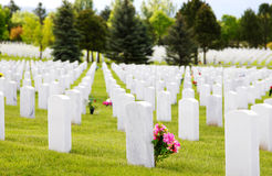 Headstones at Military Cemetery. Rows of white granite headstones at a National Military Cemetery after Memorial Day (shallow focus on headstone with pink stock images