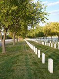 Headstones at National Cemetary. Headstones at National Cemetery with trees at sunset Stock Photo