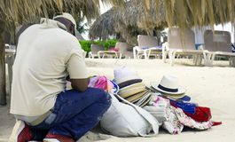 The headwear salesman sat down to rest on the beach of Punta Cana, Dominican Republic. stock images