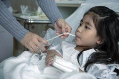 Heal kid patient drink water hospital bed. Heal kid heal patient drink water hospital bed. close up shot parent hand feeding water with straw for illness asian royalty free stock image