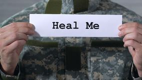 Heal Me written on paper in hands of soldier, war related diseases treatment. Stock footage stock video footage