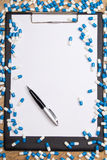 Heal of pills, clipboard and pen on wooden table Royalty Free Stock Photos