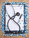 Heal of tablets, clipboard, stethoscope and pen on wooden table Royalty Free Stock Photos