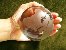 Heal the World. A glass globe held in right hand on a textured grass background Stock Photo