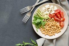 Healhty素食主义者午餐碗用鸡豆,菜,在黑暗的石背景的鲕梨,顶视图 库存图片