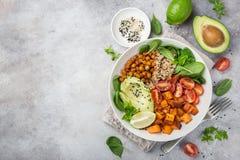 healhty vegan lunch bowl. Avocado, quinoa, sweet potato, tomato, spinach and chickpeas vegetables salad stock photo
