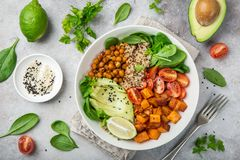 Healhty vegan lunch bowl. Avocado, quinoa, sweet potato, tomato,. Healhty vegan lunch bowl with ingredients. Avocado, quinoa, sweet potato, tomato, spinach and stock photo
