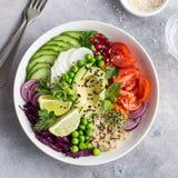 Healhty vegan lunch bowl. Avocado, quinoa, tomato, cucumber, red Royalty Free Stock Image