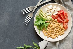 Healhty vegan lunch bowl with chickpea, vegetables, avocado on the dark stone background, top view stock images