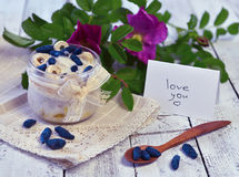 Healhy breakfast with berries, love you text on note, spoon and wild rose flowers on planks Stock Photos